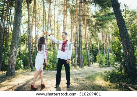 beautiful young couple in love in their national costumes. Portrait of a boy and a girl outdoors in embroidered shirts. Couple in love walking in the woods