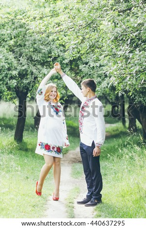 beautiful young couple in love in their national costumes. Portrait of a boy and a girl outdoors in embroidered shirts.