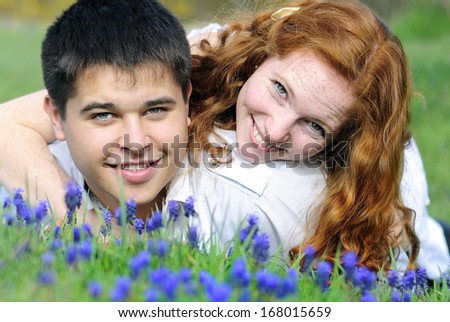 beautiful young couple in love middle of a green meadow with blue flowers - stock photo