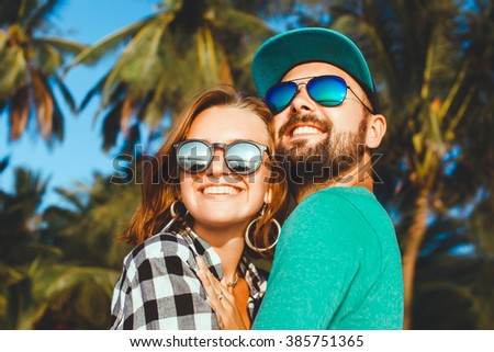 beautiful young couple in love together, girlfriend and her boyfriend in the cap sunglasses, plaid shirt , posing on the beach in Miami California outdoor portrait, close up,hipster, beard man husband - stock photo