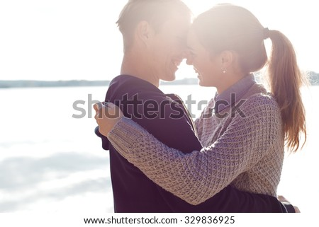 Beautiful young couple in love walking on the shore of the lake at sunset in the rays of bright light - stock photo