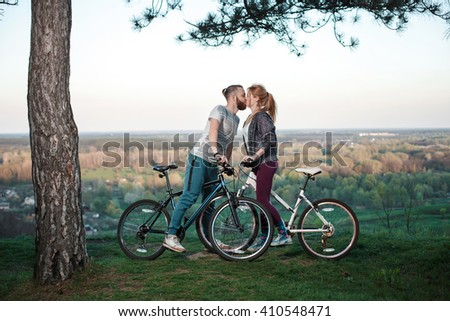 Beautiful young couple in love walking with bicycles, kissing and hugging. Stand near the bikes. The concept of active rest - stock photo
