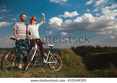 Beautiful young couple in love walking with bicycles, looking towards the beautiful nature and the blue sky. The concept of active rest - stock photo