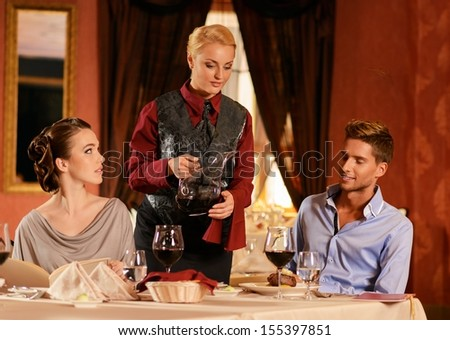 Beautiful young couple in restaurant and waitress pouring wine  - stock photo