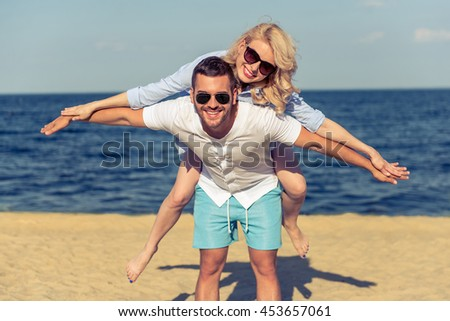 Beautiful young couple in sun glasses is looking at camera and smiling. Girl is spreading hands while sitting pickaback, sunny beach in the background - stock photo
