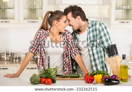 Beautiful young couple in the kitchen while cooking. - stock photo