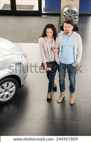 Beautiful young couple in the showroom, choosing a car. Top view. - stock photo