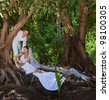 beautiful young couple in wedding dress on the tree - stock photo