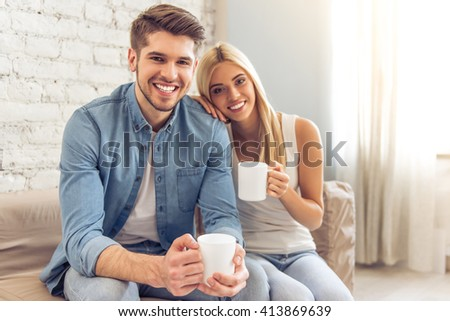 Beautiful young couple is holding cups of drink, looking at camera and smiling while sitting on sofa at home - stock photo