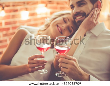 Beautiful young couple is holding glasses of wine and smiling while celebrating at home