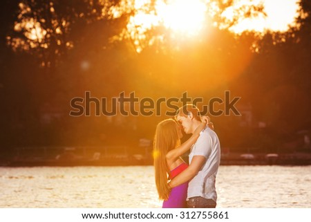Beautiful young couple is kissing at golden summer river sunset background. - stock photo