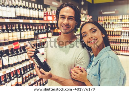 Beautiful young couple is looking at camera and smiling while choosing wine in the supermarket
