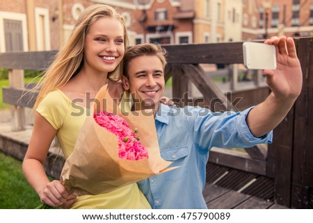 Beautiful young couple is making selfie using a smart phone and smiling while sitting outdoors. Girl is holding flowers