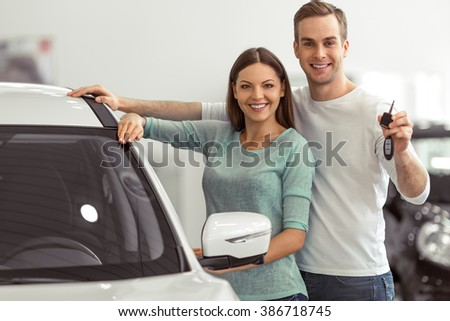 Beautiful young couple is smiling and looking at camera while leaning on their new car in a motor show. Man is holding car keys - stock photo