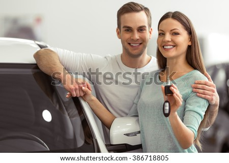 Beautiful young couple is smiling and looking at camera while leaning on their new car in a motor show. Woman is holding car keys - stock photo