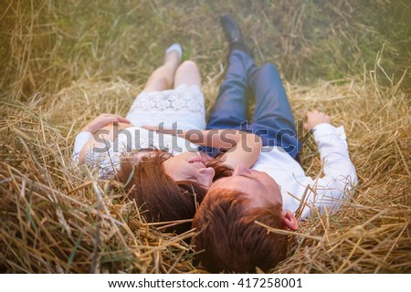 Beautiful young couple is tenderly embracing at rural haystacks summer field background. - stock photo