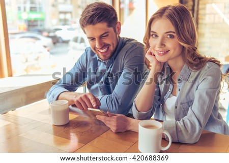 Beautiful young couple is using a smartphone, talking and smiling while sitting in the cafe. Girl is looking at camera - stock photo
