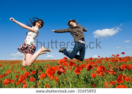 Beautiful young couple jumping in the poppy field, motion blur - stock photo