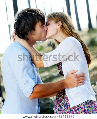 beautiful young couple kiss outdoors in the forest, true love and passion - stock photo