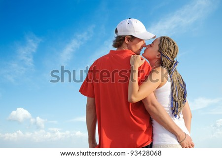 Beautiful young couple kissing against blue sky - stock photo