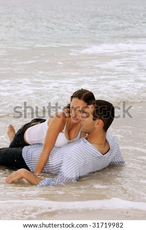 Beautiful young couple laying in the water at the beach, on top of each other, fully clothed. Heads touching looking to the left. With copy space on top. - stock photo