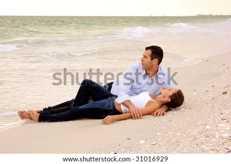 Beautiful young couple laying on the beach having a conversation, their clothes are wet from the ocean - stock photo