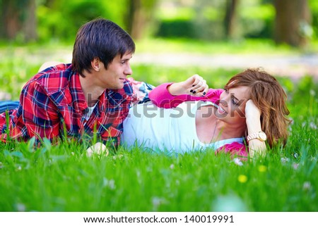 beautiful young couple lying in spring grass