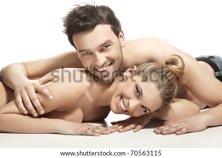 Beautiful young couple lying on the bed - stock photo