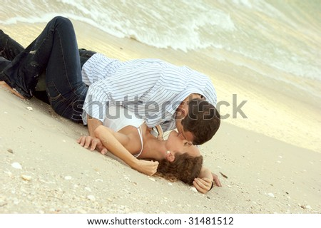 Beautiful young couple making out on the beach, their clothes are wet and the man is laying on top of the woman. - stock photo