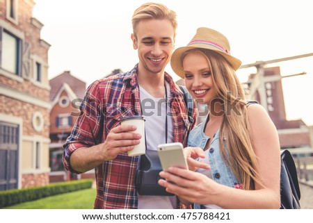 Beautiful young couple of travelers is using a smart phone and smiling while walking outdoors. Guy is holding a cup of coffee