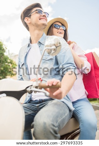 Beautiful young couple on scooter looking away, happy woman holding shopping bags. - stock photo