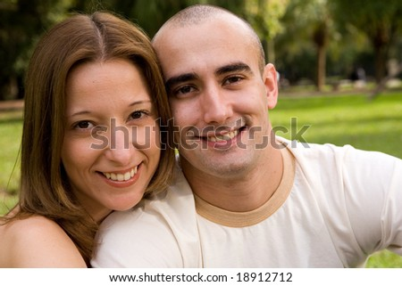 beautiful young couple on the park in sunny day - stock photo