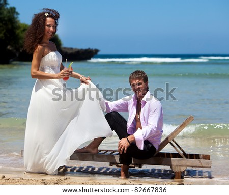 Beautiful young couple on vacation near the ocean with a cocktail in hand - stock photo