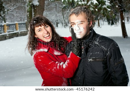 Beautiful young couple playing outdoors in snow.