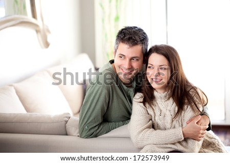 Beautiful young couple posing in a living room - stock photo