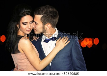 Beautiful young couple posing in the dark - stock photo