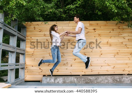 beautiful young couple posing on a background of a wooden wall at the camera - stock photo