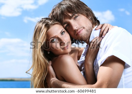 Beautiful young couple posing together over blue sky. - stock photo
