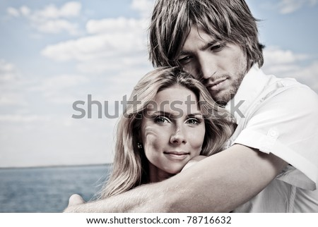 Beautiful young couple posing together over the sea. - stock photo