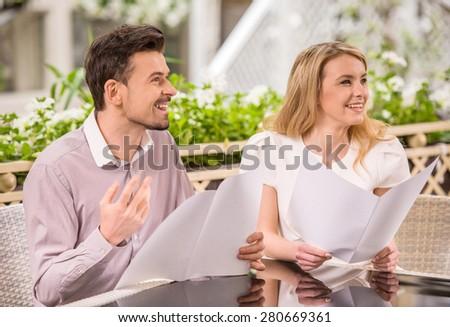 Beautiful young couple reading menu at restaurant. Romantic date. - stock photo