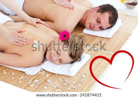 Beautiful young couple receiving a back massage against heart - stock photo