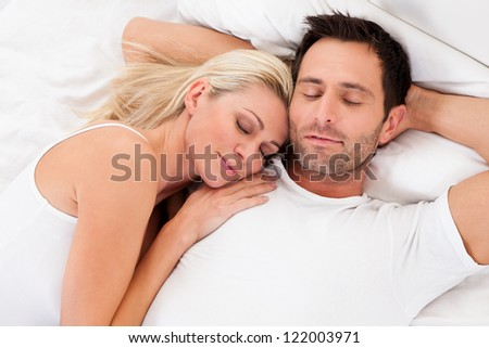 Beautiful young couple relaxing in bed at home - stock photo