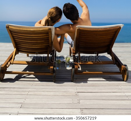 beautiful young couple resting in deck chairs at the pool - stock photo