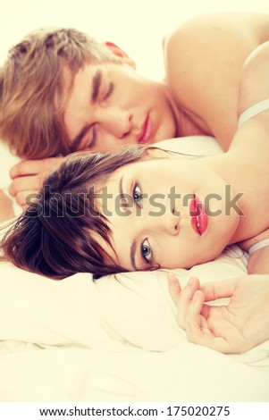 Beautiful young couple sleeping in bed.  - stock photo
