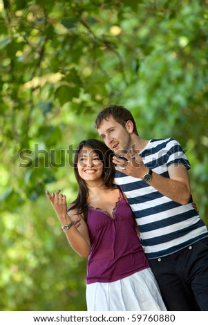 Beautiful young couple smiling and walking outdoors - stock photo