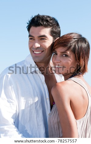 Beautiful young couple smiling together in a sunny summer day