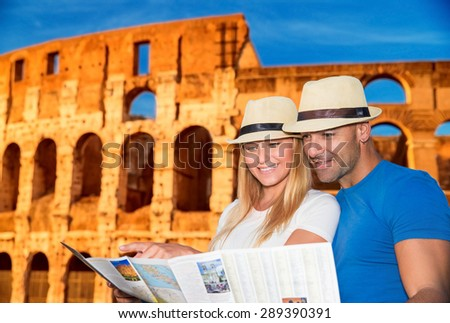Beautiful young couple standing near Coliseum and looking in the map, searching right direction to next sightseeing, active summer vacation in Rome, Italy, Europe - stock photo