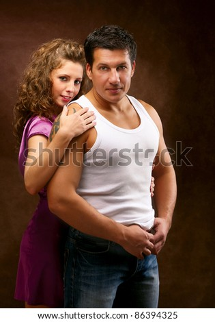 Beautiful young couple standing on brown background - stock photo