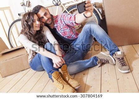 beautiful young couple take a selfie after moving - stock photo