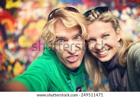 Beautiful young couple taking selfie of themselves as they make funny faces - stock photo